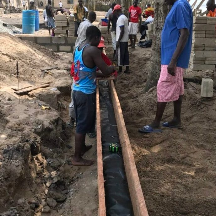 Love Africa Project crew adding vapour barrier to foundation walls for public washroom in Saltpond, Ghana