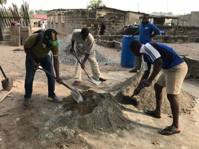 Crew mixes concrete for public washroom building that will have 20 toilets in Saltpond, Ghana