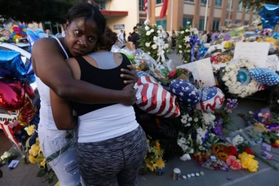 A friend supports Keaka Wallace (R) who says she was a patrol partner of slain DART officer Brent Thompson, weeps as she leaves a makeshift memorial at Dallas Police Headquarters following the multiple police shooting in Dallas, Texas, U.S.,July 8, 2016. REUTERS/Carlo Allegri - RTSH11P