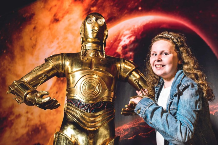 Kaelyn Dudley (aged 10) is pictured greeting C-3PO as one of Europe's largest privately owned collections of robots, cyborgs and androids arrive at Titanic Belfast for its ROBOTS Summer exhibition (26th June – 13th September). For more information or to buy tickets, visit www.titanicbelfast.com. Picture: Elaine Hill