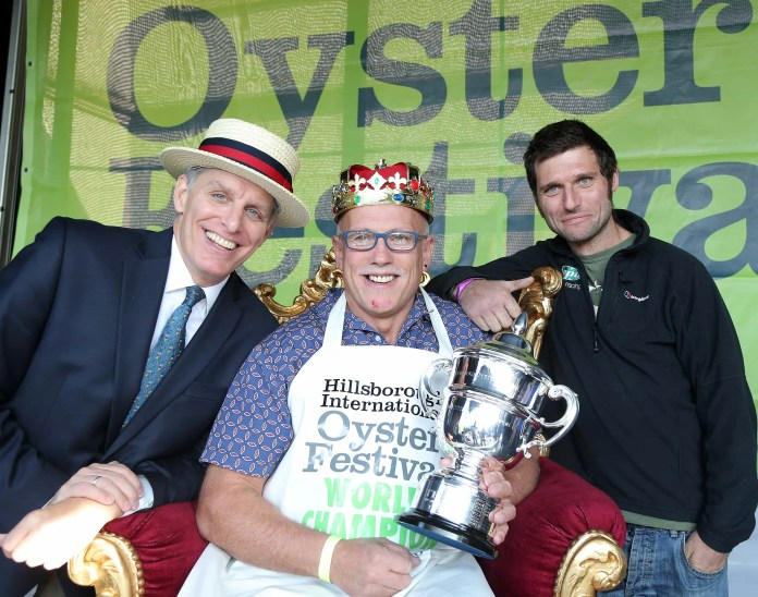 5 September 15 -   Picture by Darren Kidd / Press Eye. Pictured celebrating with the still undefeated World Oyster Eating Championship Colin Shirlow (centre) are compere George Shea (left) who flew in from New York for the competition and motor racing legend Guy Martin who was a guest judge at the TrustFord Soapbox Derby. Both of these superb events took place at the 23rd annual Hillsborough International Oyster Festival. Colin Tops The Table Again: They came, they swallowed but as always they failed to conquer. Today saw the World Oyster Eating Championship as part of the 23rd Hillsborough International Oyster Festival. This years event included a special challenge from a diminutive professional eater, Michelle Lesco, who flew all the way from Arizona  to take on Oyster King Colin Shirlow and together guzzle hundreds of oysters.  However as always, local champ Colin Shirlow ran away with the contest. Taking part in his 11th year, the Dromore man managed to put away a ÔshuckingÕ  235 oysters in just three minutes - breaking his own World Record of eating 233 oysters in 3 minutes, which he set in 2005. Colin was jubilant when he collected his crown saying, ÒIt's astonishing that I've won the championship yet again and I am delighted to have beaten my record! He went on, ÒEven if I didn't win I would still take part in the contest. The Hillsborough Oyster Festival is a fantastic event. It's so much fun and shows some of the best hospitality that Hillsborough has to offer.Ó It's hardly surprising the former boxer managed to beat the other contenders to the title Ð he's done exactly the same thing every single one of the 11 years he's taken part in the competition and this win was on the 10th anniversary of his World Record, which until now he had only managed to equal in 2013. As ever Colin puts his unusual technique down to the training he received during his boxing days. ÒIt's about speed and rhythm,Ó he explained. ÒYou can't get either until you focus but once you f