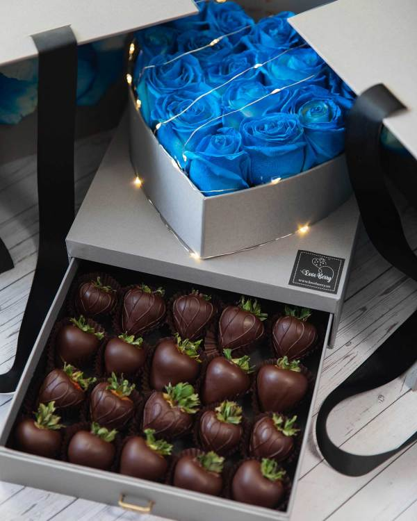 Blue roses and milk chocolate strawberries