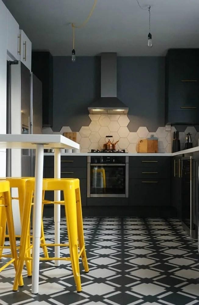 dark kitchen with monochrome floor and yellow bar stools