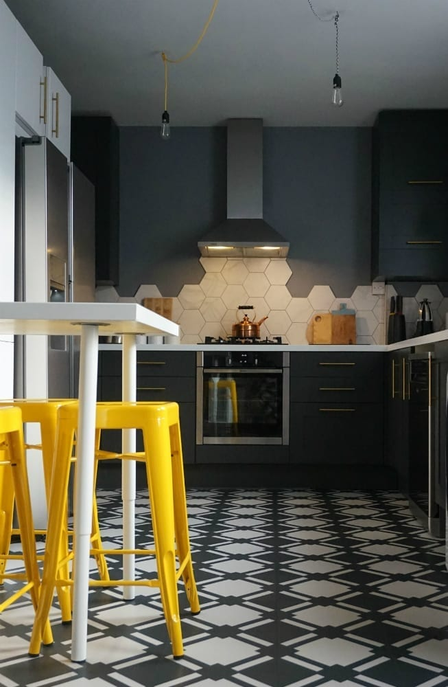 dark kitchen with monochrome floor and yellow bar stools