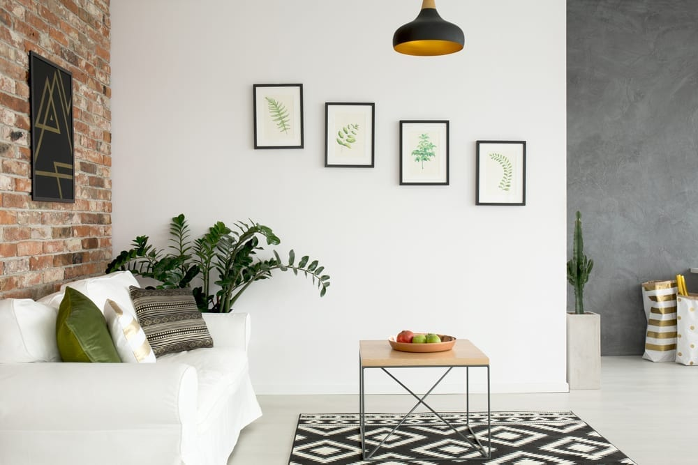 Light and bright living room wall with white sofa, green accents and brick wall