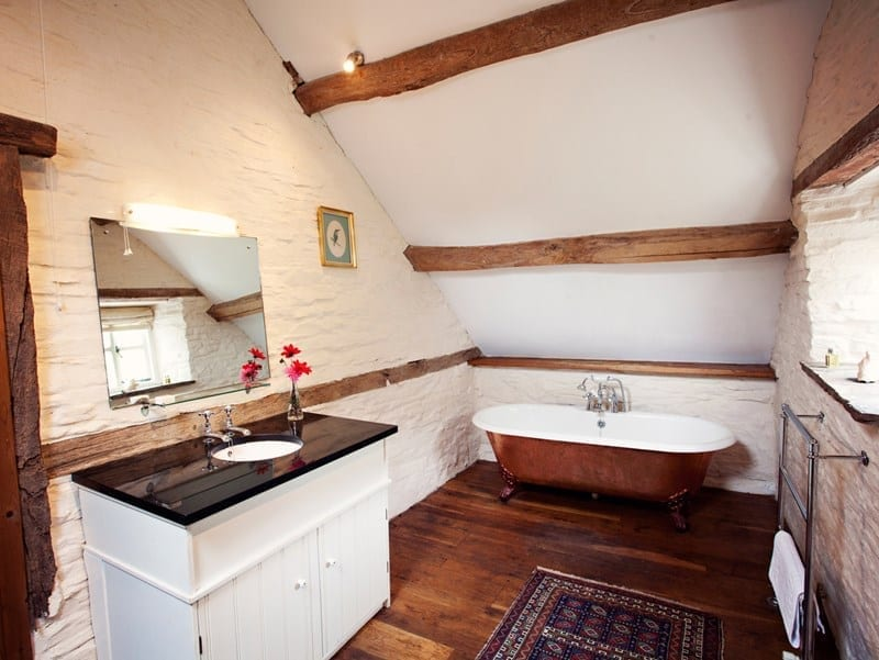 Old cottage bathroom with sloped ceiling and beams