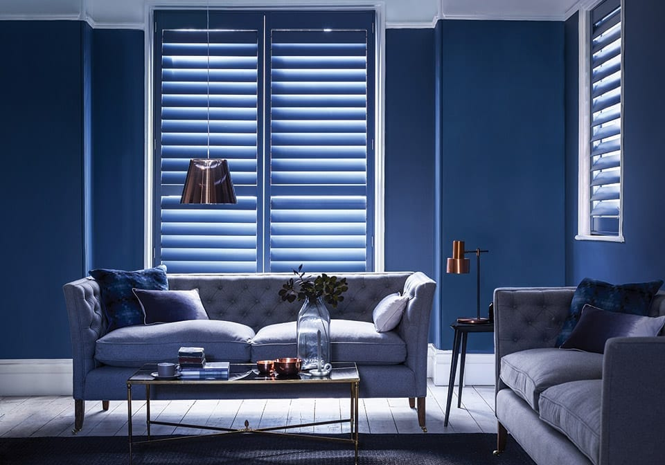 dark blue full height window shutters in a dark blue stylish living room