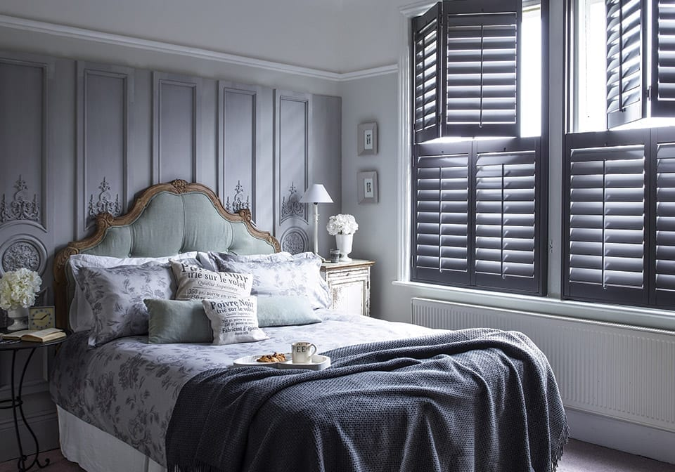grand bed in a room with grey window shutters