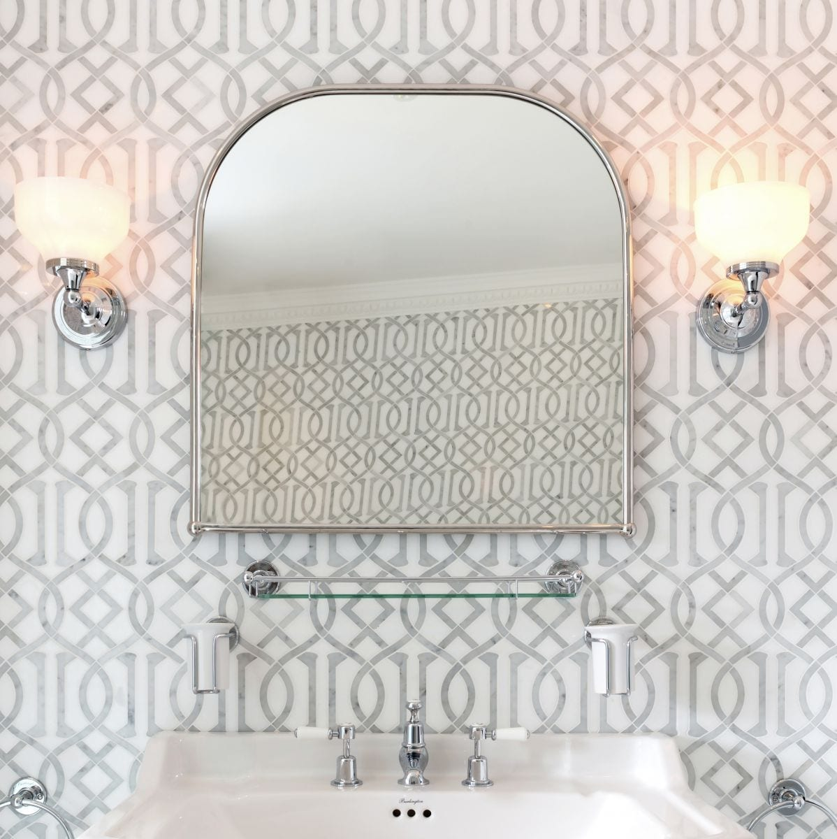 oval bathroom mirror with background of silver wallpaper and wall lights