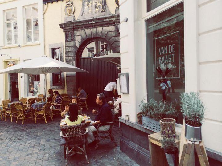 Van de Kaart Op een van de gezelligste pleintjes van Maastricht, het Onze-Lieve-Vrouweplein, vind je Restaurant Van de Kaart. Dit is een gezellig restaurant, met een verrassende kaart. Veel kleine hapjes en broodjes voor ontbijt, lunch & diner, maar ook grote gerechten. Het terras is fantastisch. Het plein ademt in de bourgondische sfeer van de stad. Binnen is de sfeer heel vlot. Steigerhouten tafels, lange banken en hoge en lange tafels afgewisseld. Het ziet er top uit! De prijzen zijn echt wel ok. Voor een gemiddeld broodje betaal je ongeveer zeven euro. Voor een hoofdgerecht zo'n zestien euro. Goed om te melden: op de kaart staan ook vier vegatarische gerechten. Website: www.vandekaartmaastricht.nl/Adres: Onze-Lieve-Vrouweplein 28, Maastricht Openingstijden: Dagelijks vanaf 10.30 uur.De keuken sluit om 22.00 uur