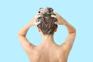 Beautiful young woman washing hair against color background, back view