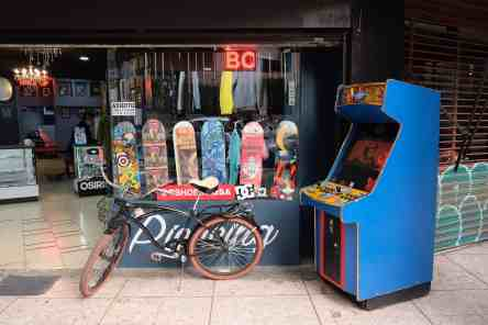 A bike and pac man machine in front of a skate shop in Roma Norte