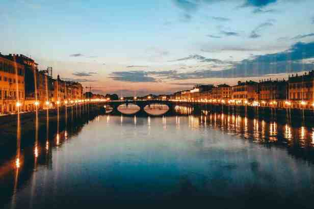 The gorgeous Arno river as the sun is going down and the street lights start to reflect on the water.