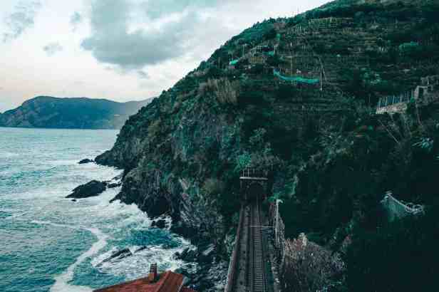 Train going through the cliffside by the water in Cinque Terre