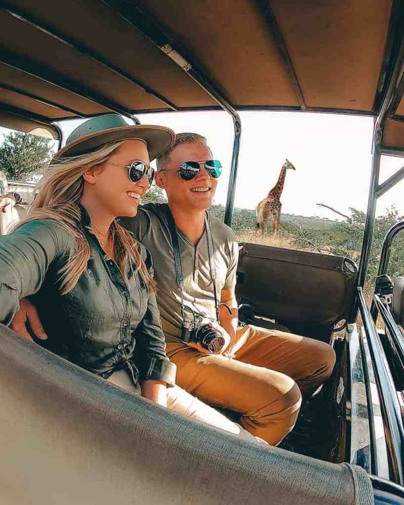 Couple smiling in a safari jeep with a Giraffe in the background
