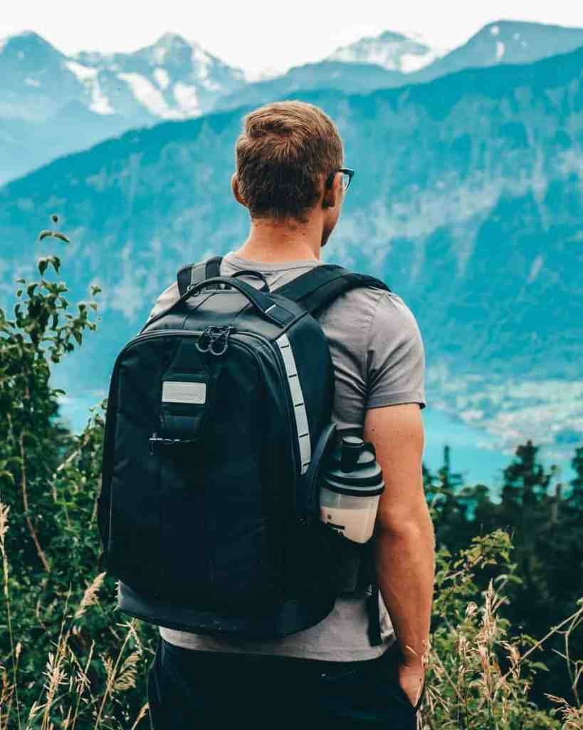 Man standing in the swiss alps looking out wearing the PolarPro backpack, the best camera backpack