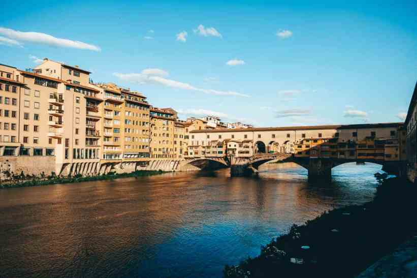 Ponte Vecchio bridge enclosed with many shops over the Arno river in Florence.