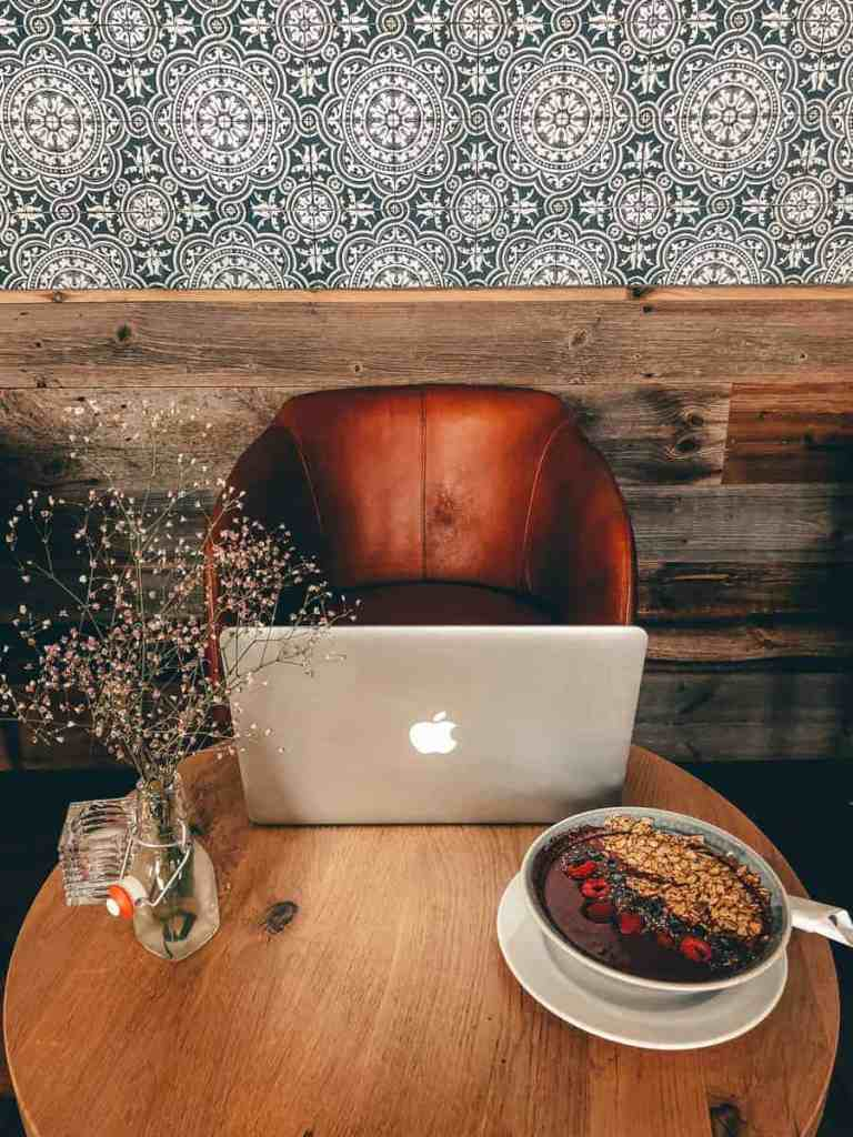 Macbook pro sitting on a wooden table next to flowers and an acai bowl at a coffee shop