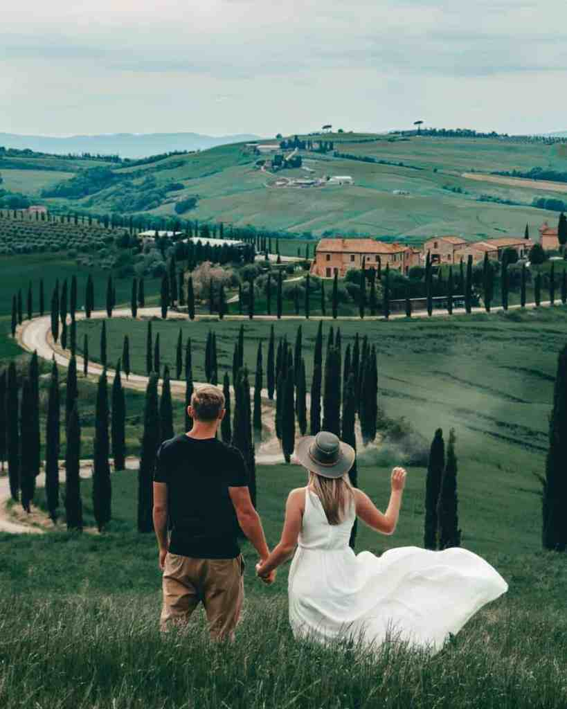 Couple holding hands looking away at the winding roads and beautiful hills of Tuscany