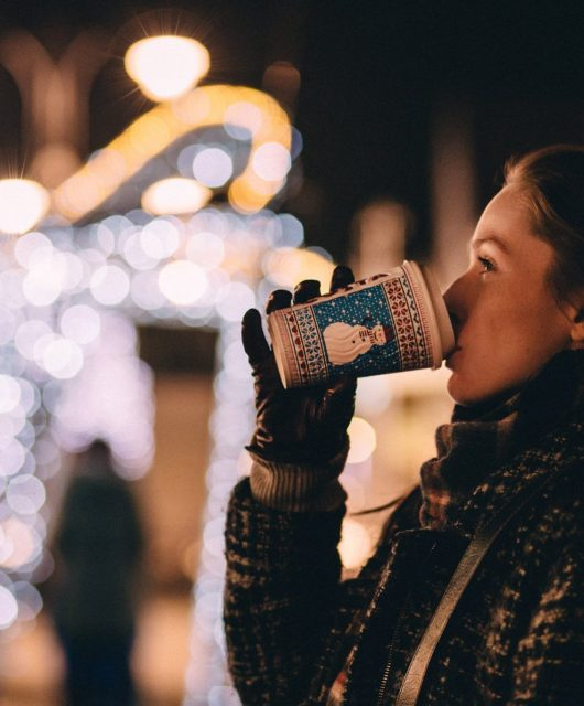 Girl drinking coffee on a during the holiday season on Christmas night