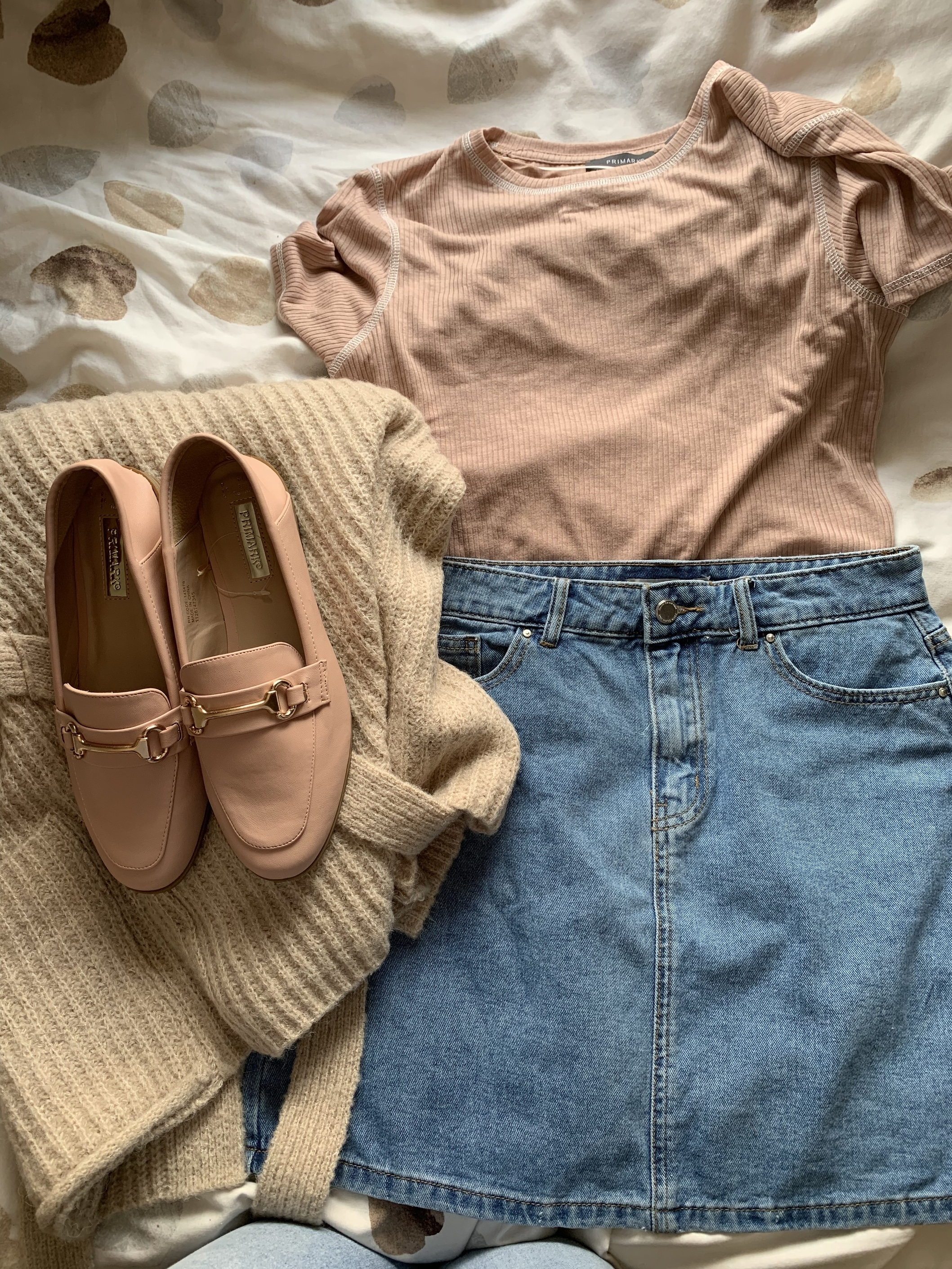 Fashion flatlay of a pink t-shirt, a denim skirt, a camel cardigan and pink loafers with a gold bar