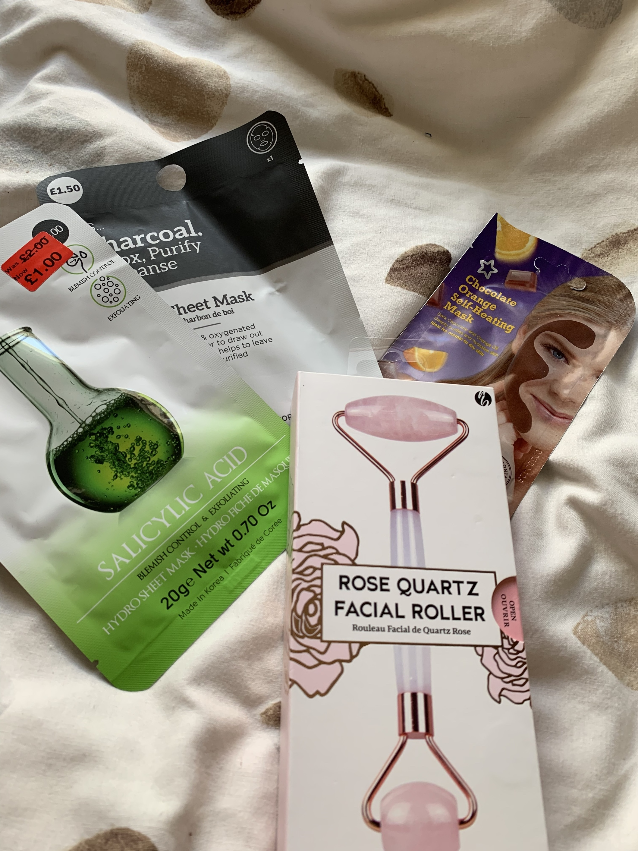 Rose quartz face roller, 2 sheet masks for acne-prone skin and a chocolate orange self-heating face mask.