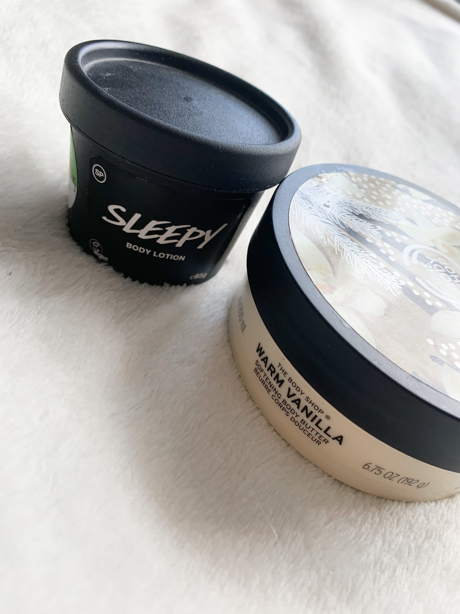 Lush's sleepy lotion and the body shop warm vanilla body butter on a white fluffy blanket