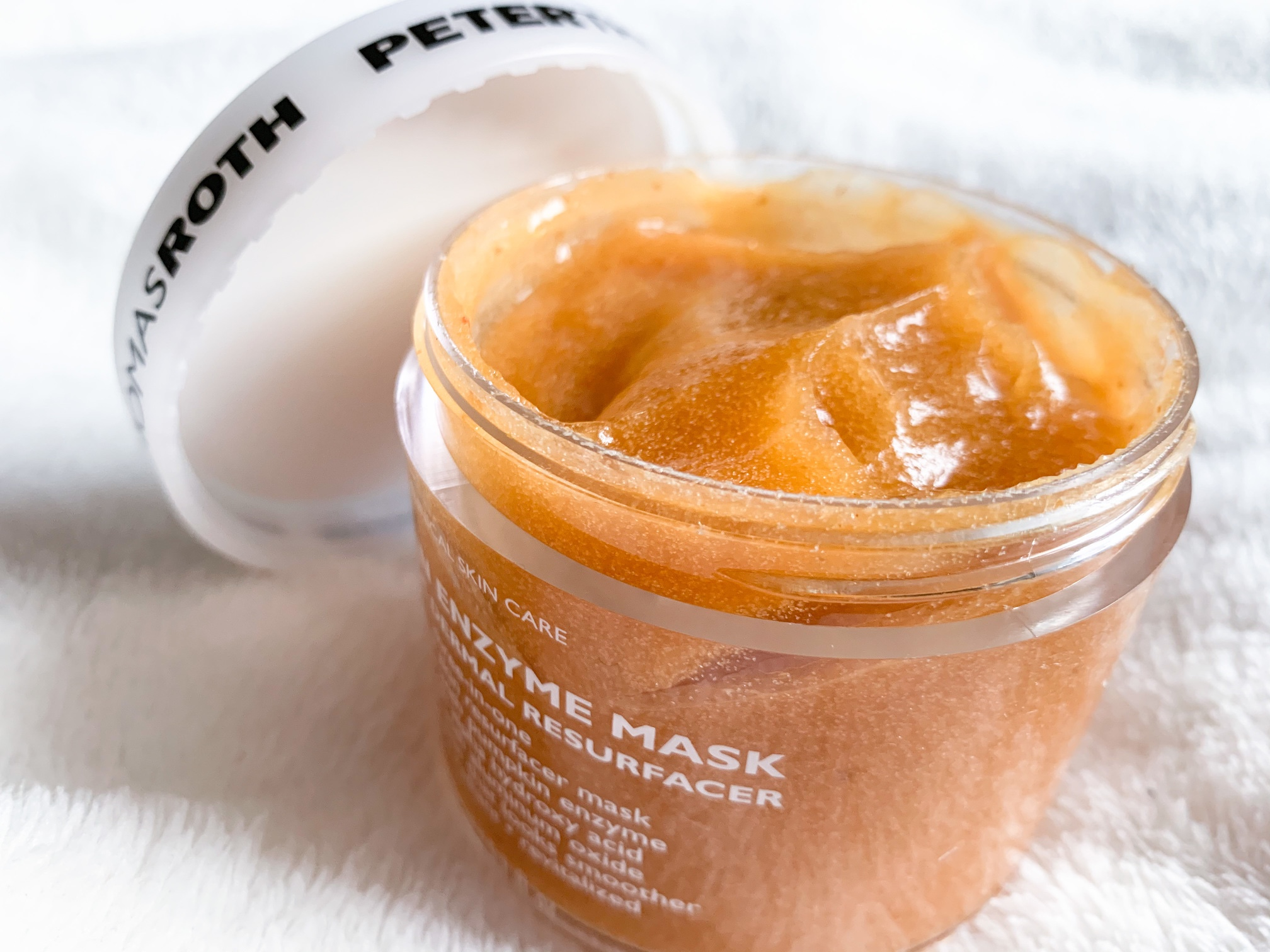Peter Thomas Roth pumpkin enzyme face mask on a white blanket with the lid off