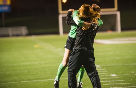 Goalie Lauren Parker hugs her coach after Loveland's win