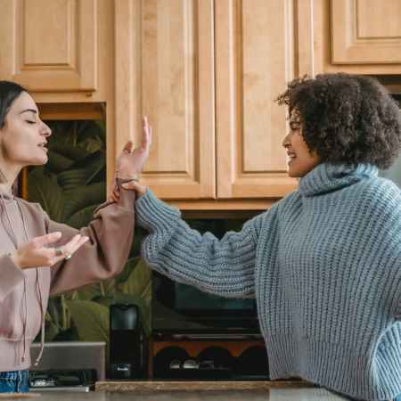 Image of a black and latinix woman arguing in a kitchen