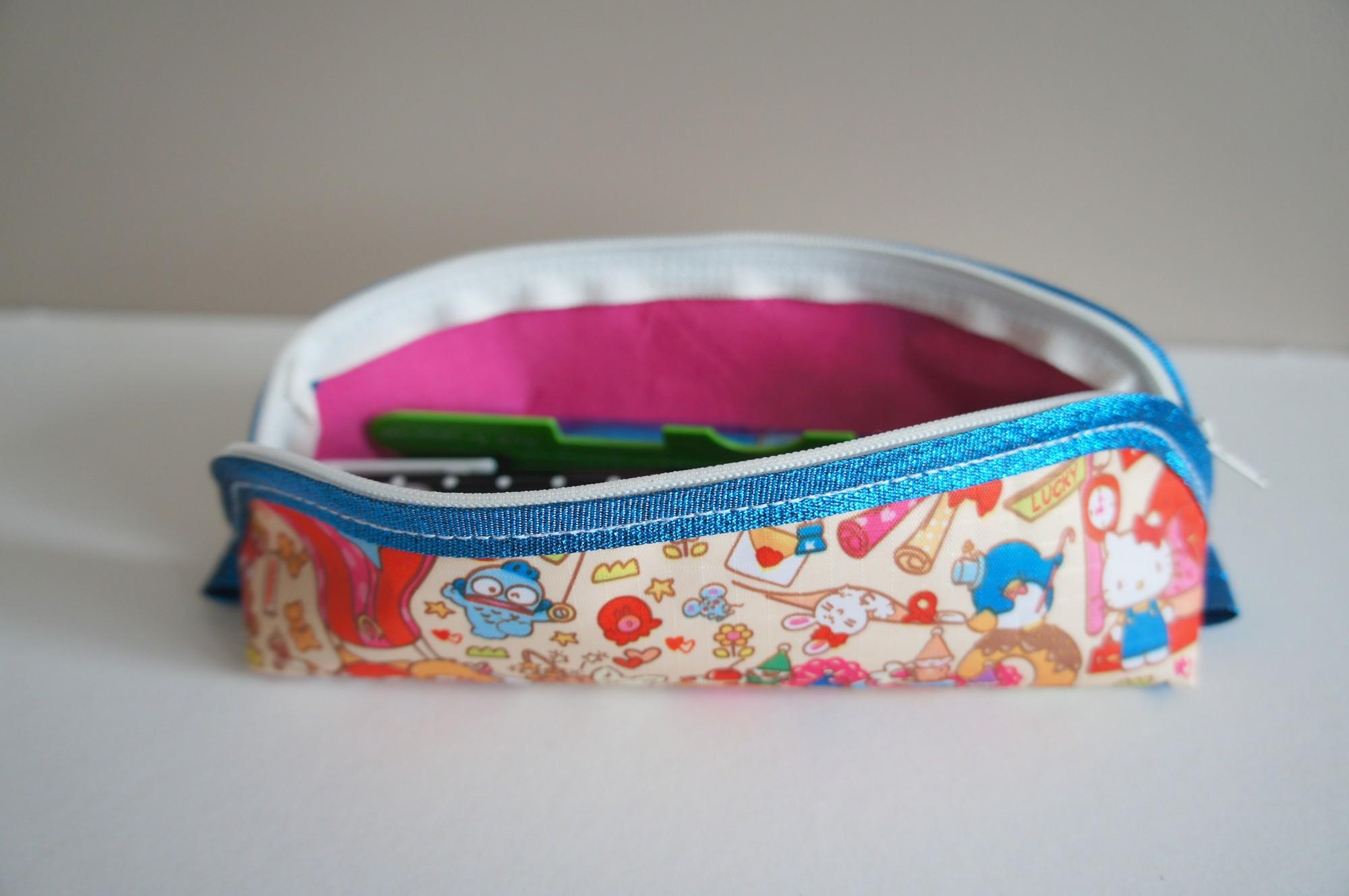 Intérieur rose de la petite trousse à stylos trop mignonne, avec biais bleu flashy pailleté