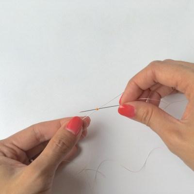 Passez votre seconde aiguille dans la perle dans le sens opposé. Vos aiguilles doivent se croiser dans la perle.
