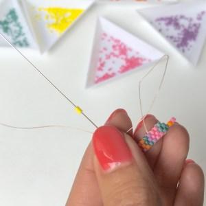 Votre fil ressort au bon endroit, vous pouvez enfiler directement 2 perles jaunes