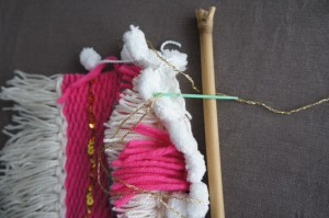 Pour accrocher le tissage au support : à l'aide d'une aiguille à laine, passer un fil dans les fils de chaîne puis autour de votre baguette. Nouez les extrémités, et c'est terminé !
