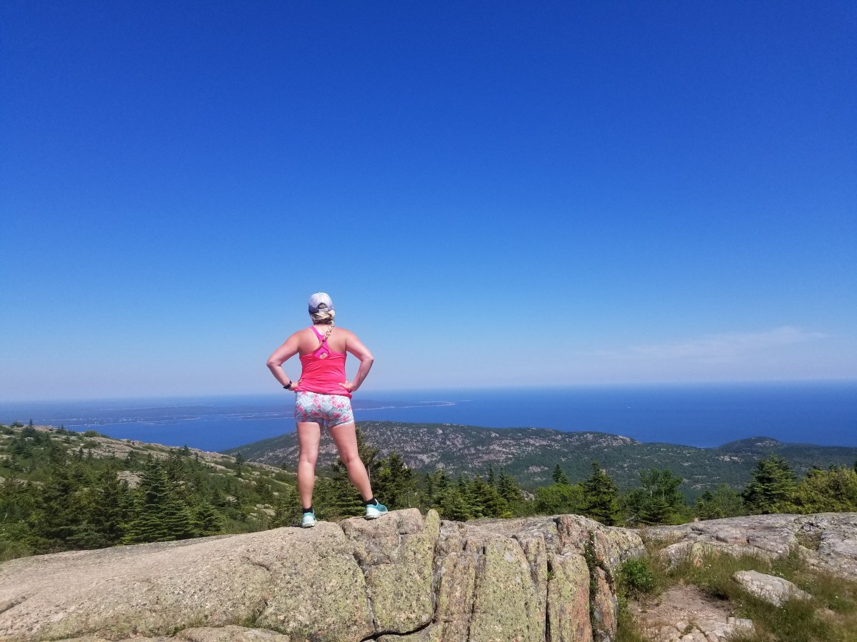 Woman hiker on the summit of Cadillac Mountain