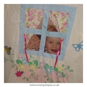 childs face looking out their cottage teepee window