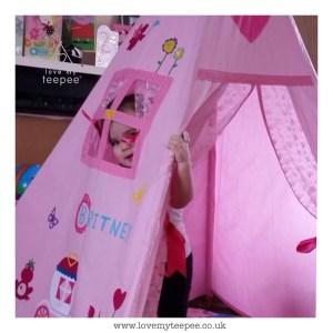 little girl peeking out of the teepee window
