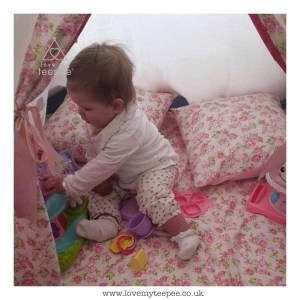 little girl playing with a tea set inside the rose teepee