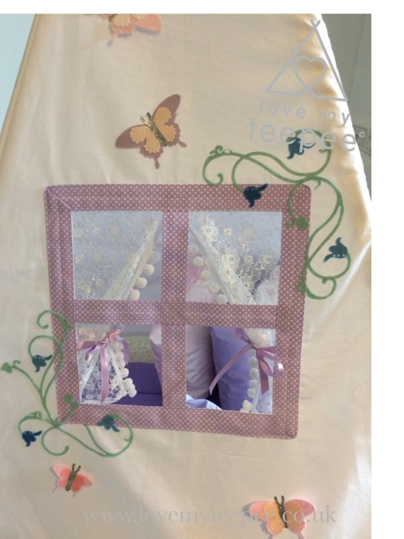 lilac window frame with lace curtains on the side of a teepee decorated with bluebells and butterflies