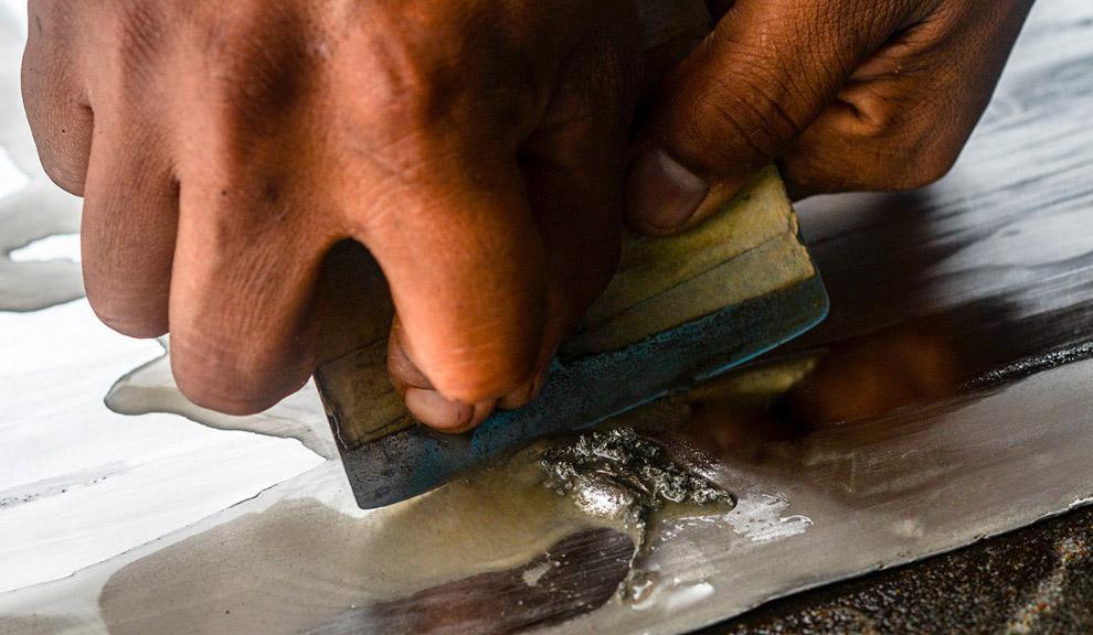 Вот как раз рабочий соскребает золото-ртутную амальгаму с алюминиевого листа