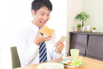 食事中にスマホをいじる男性