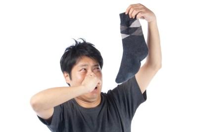 臭い靴下を持つ男性