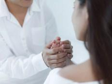 彼女の手を握る男性