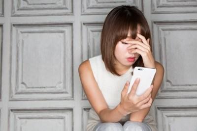 スマートフォン・顔を覆う女性