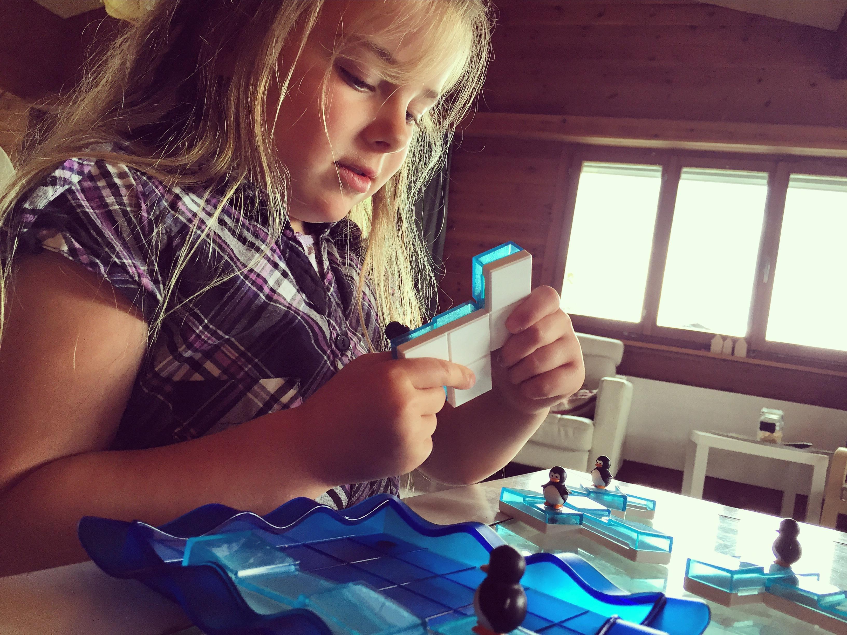 Eva snapt eindelijk hoe het pinguinspel van Smartgames werkt en speelt er lekker mee