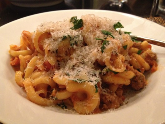 Lamb ragu with Girelle in a bowl with grated Romano cheese and cracked black pepper.
