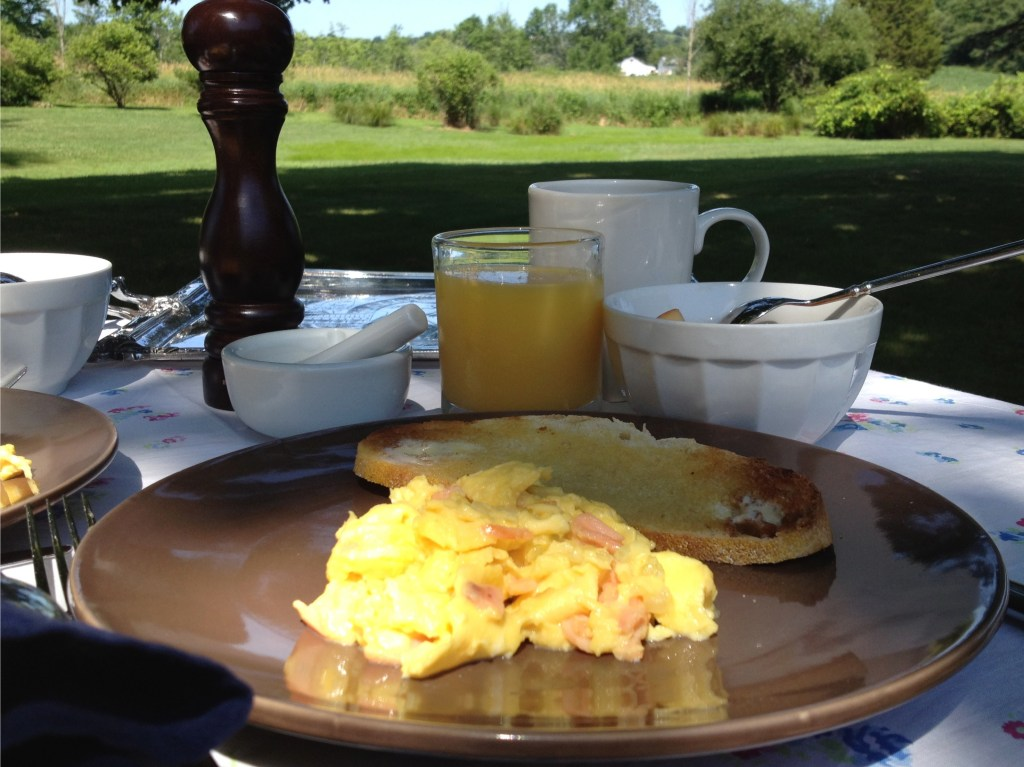 Breakfast outside with eggs, toast, and orange juice.