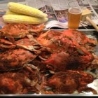 Hard shell crabs and beer on a metal platter.