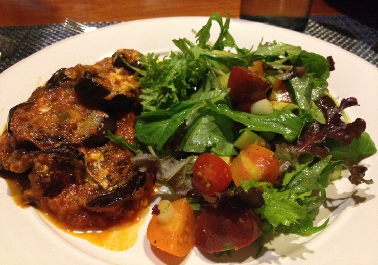 Eggplant Parmigiano and farm stand salad on a white plate.