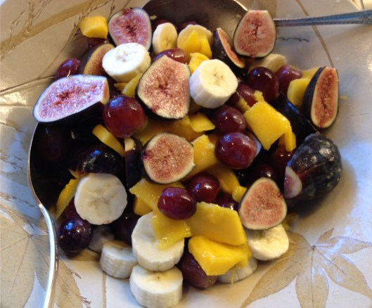 Fruit salad with black mission figs, mango, red grapes and banana.